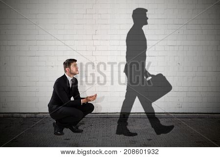 Young Homeless Beggar Looking At Shadow Walking With Briefcase
