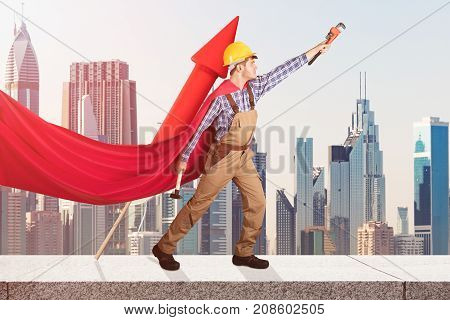 Superhero Handyman With Worktools And Red Rocket Standing On Wall Against City Buildings