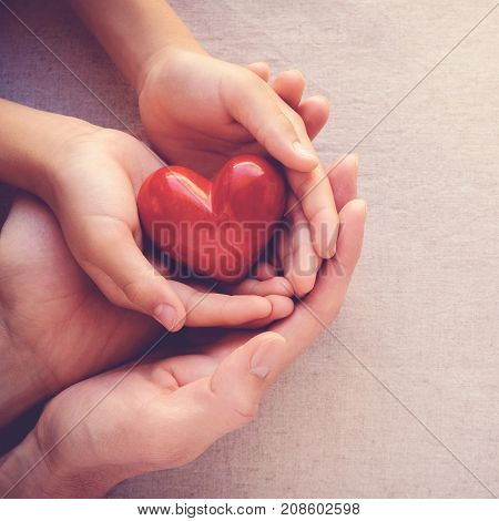 adult and child hands holiding red heart health care love and family concept