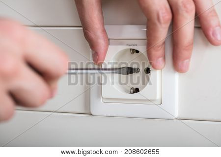 Close-up Of Person's Hand Fixing Electrical Socket With Screwdriver