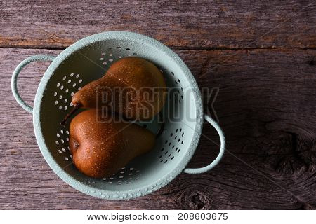 Top view of two Bosc Pears in a colander on a rustic wood sruface.