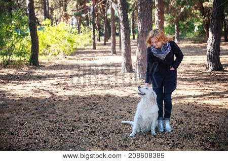 A girl in a dark coat, a blonde walks with a dog in the park