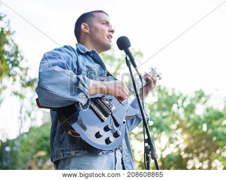 Handsome young man plays the guitar and sings songs in a group on the street in a park in a denim jacket on a blurred background. Music concept.