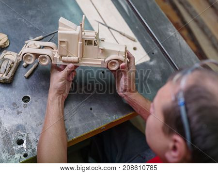 Wooden car close-up that the master collects with the hands of the master against the gray desktop background