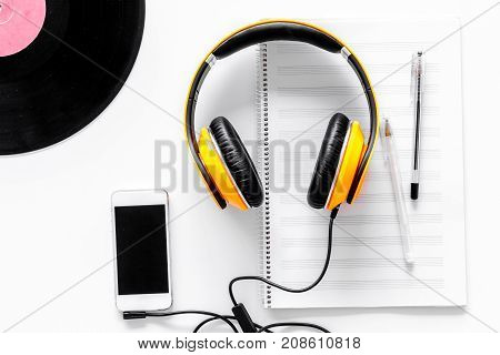 Accessories of contemporary composer. Headphones. phone, vinyl record, music notes on white background top view.
