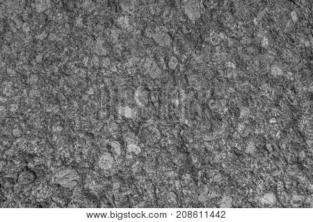 texture granite  has a gray tint.  fragment of stone boulder close-up.