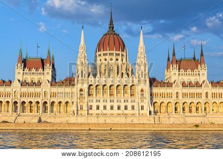 The symmetrical main facade and the central dome of the Hungarian Parliament Building overlook the River Danube - Budapest, Hungary
