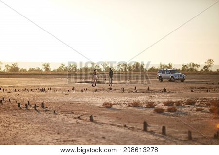 Young couple on a travel trip near a new modern automobile on a spacious natural background. Beautiful nature landscape. Copy space.