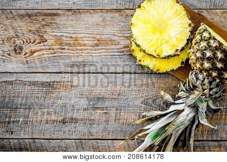 Sliced pineapple on wooden background top view.