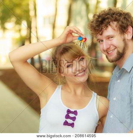 Real estate and family concept. Couple showing their new house keys