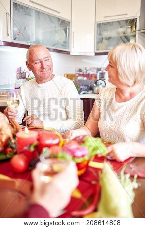 Happy family having dinner on the holiday table at home and thank God for food. Tasty baken chicken with vegetables on the table. Close-up of grandparents. Food concept.