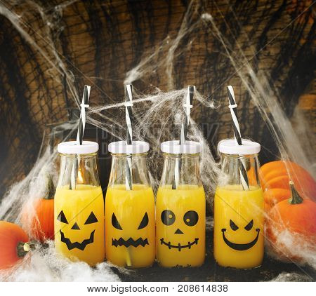 Orange coctail in bottle for fall and halloween parties toned image