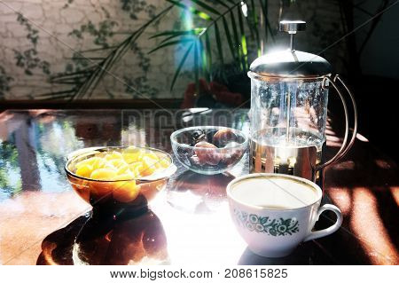 Tea time set on table: cup tea pot and dishes: dried apricots and dates. Raw lifestyle healthy food concept. Arabic traditional sweets