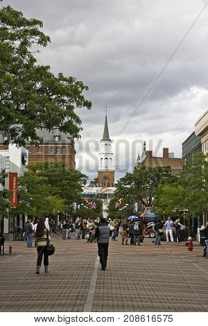 Burlington Vermont - October 5 2009 -- Vertical looking down the main street of the Church Street Marketplace with crowds of people street vendors shops and the First Unitarian Church at the end of the street in Burlington Vermont on a cloudy gray day in