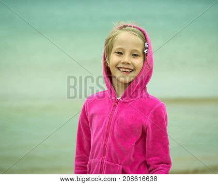 Portrait Of A Smiling Girl In A Red Hood Against A Cold Ocean.