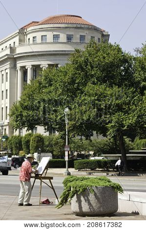 Washington, DC - September 14, 2009 -- Vertical of the a man painting the street scene and stately building architecture in downtown Washington, set against a blue sky on sunny afternoon in September.
