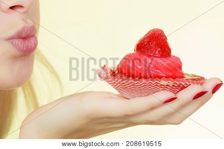 Sweets fat food sugar concept. Woman holding sweet strawberry cupcake sending air kisses.