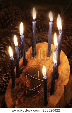 Crafted wood log Hanukkah menorah with star of David inset, candles lighted