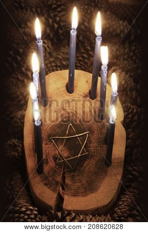 Front view of a wood log Hanukkah menorah with Star of David wire inset, candles lighted