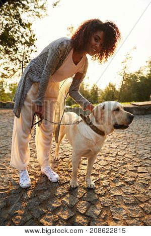 Happy african lady with curly hair hugging her white friendly dog while walking in park