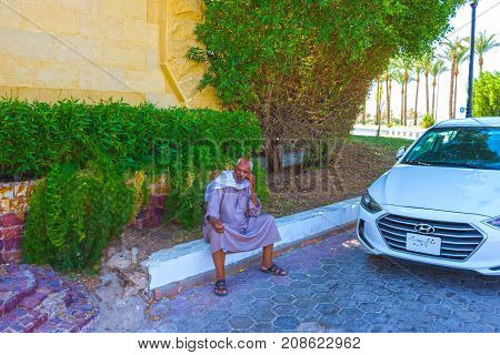 Sharm el Sheikh Egypt - September 27 2017: The local man taxi driver sitting and talking on mobile phone near the car at Sharm el Sheikh Egypt on September 27 2017