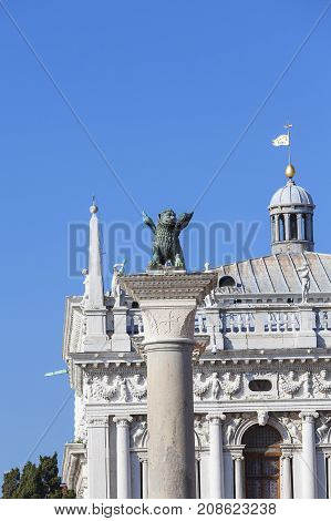 Column of San Marco and National Library of St Mark's on Piazza San Marco Venice Italy. Lion of Saint Mark is ancient bronze winged lion sculpture symbol of the city