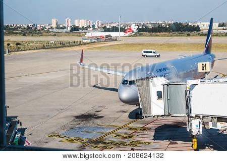 Modern Passenger Airplane Parked To Terminal Building Gate Is Seen Through Of Window