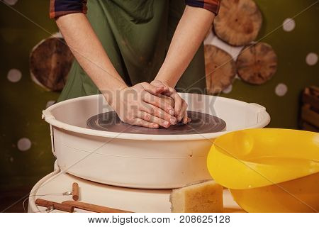 A young woman in a plaid shirt and jeans sculpts a clay bowl on a potter's wheel in a bright beautiful workshop decorated with wooden circles