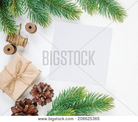 Christmas frame consisting of fir branches cones and gift boxe tied with hemp twine on a white background with space for text. Flat lay composition for greeting cards websites social media magazines bloggers artists etc. Christmas wallpaper