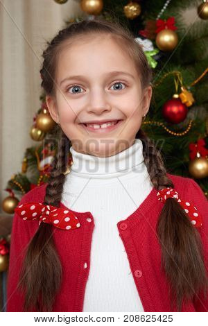 Girl portrait near christmas tree, happy holiday and winter celebration, dressed in red
