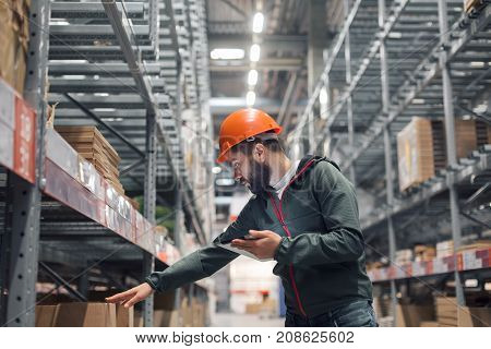 Warehouse manager checking his inventory in a large warehouse. using the tablet via the Internet is checking stock availability