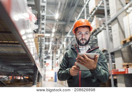 wholesale, logistic, people and export concept - manager or supervisor with tablet at warehouse. using the tablet via the Internet is checking stock availability poster