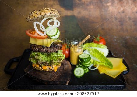 Hamburger with flying ingredients. Tasty smoked grilled and glazed beef burger with lettuce, cheese and vegetables on vintage background.