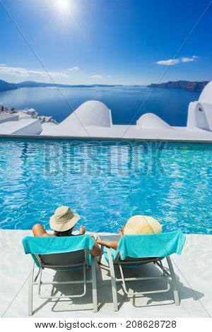 Couple on summer holidays relaxing by the swimming pool  in Santorini Greece