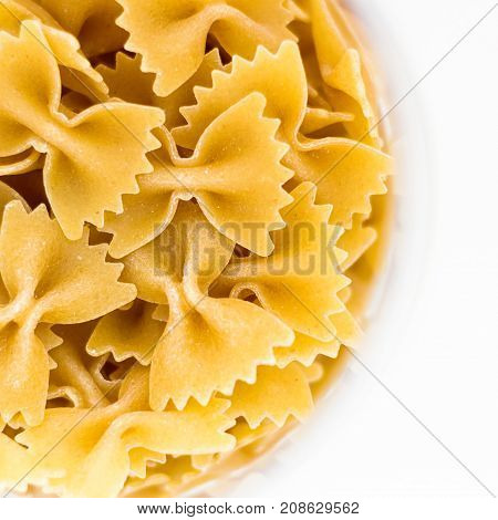 Bow tie pasta in bowl isolated on white background top view.