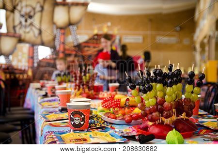 covered festive table in pirate symbolism with food on a pirate party