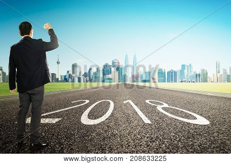 2018 new year young businessman cheer with city skyline background . Refresh and hope concept .