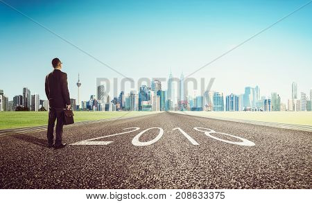 New year 2018 young businessman looking on city skyline background . Determined to start concept .
