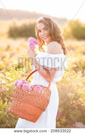 Smiling blonde girl 20-25 year old holding basket with tea roses walking in meadow. Looking at camera. Summer time. 20s.