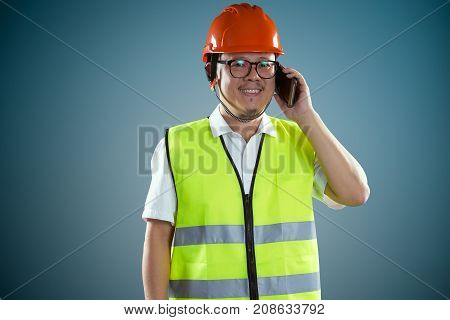 Young asian construction workers in safety helmet and using smartphone isolated on blue background