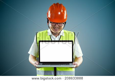 Young asian construction workers in safety helmet and using laptop with empty screen to show client something isolated on blue background .