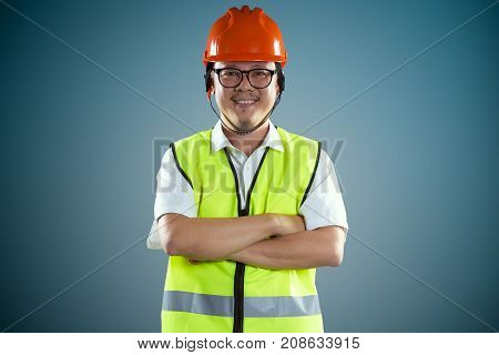 Young asian construction workers in safety helmet isolated on blue background .