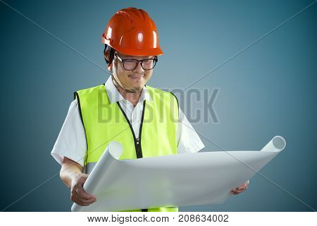 Portrait of professional construction contractor worker with hard hat and holding construction blue print plan with light blue background .