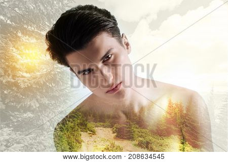 Feeling lonely. Upset boy standing against nature background while showing sadness on his face
