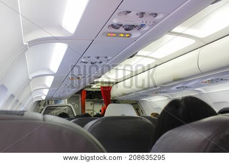 Interior of airplane with passengers.No smoking sign and seat belt sign on the airplane