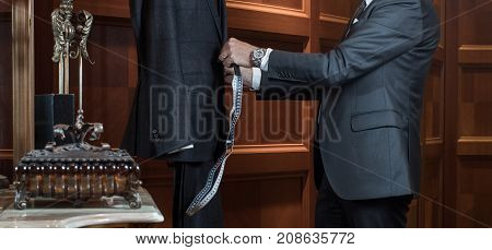 The tailor works with the dummy, measuring the costumes. Hands of a tailor man in suit in the interior of the boutique tailoring of individual suits