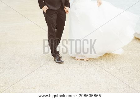 Just married loving couple in wedding dress and suit walking and holding hands on a stone jetty. Closeup half body .