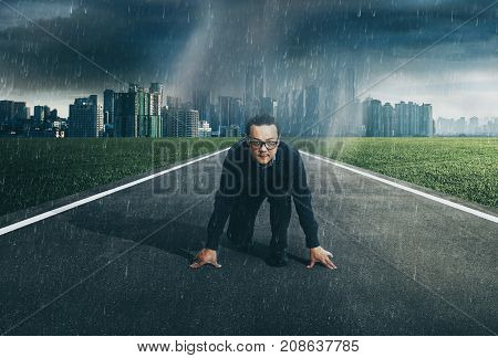 Young businessman starting position to his career with city skyline background raining day . Determined to start concept .