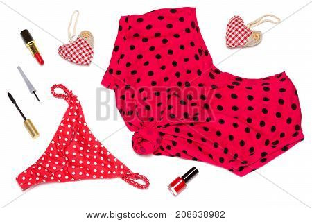 Women things on white background. Tied T-shirt and high rise panty in polka dot with red lipstick and nail polish, black eyeliner and mascara. Cute pin-up set