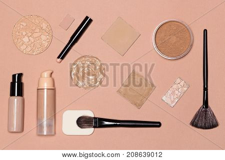 Set of foundation makeup products: concealer stick, primer, liquid and cream foundation, cosmetic powder with make up brushes. Flat lay still life
